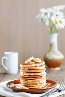 Pfannkuchen mit bananenscheiben, zum frühstück mit honig bestreut kamillen.