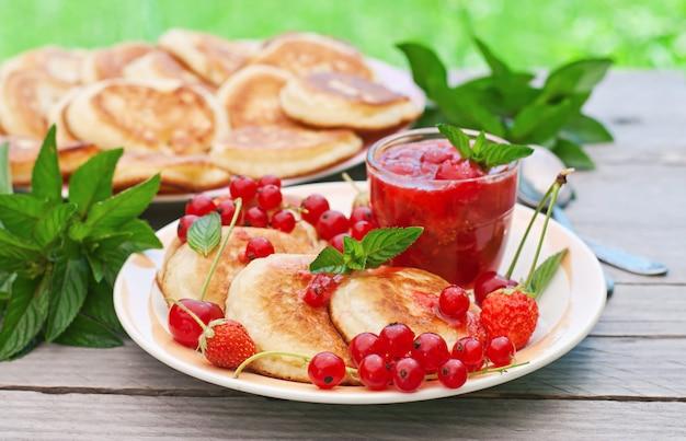 Pfannkuchen mit beeren auf einem holztisch in einem sommergarten