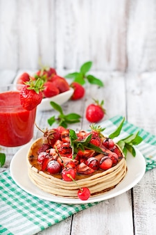 Pfannkuchen mit beeren und erdbeersmoothie im rustikalen stil