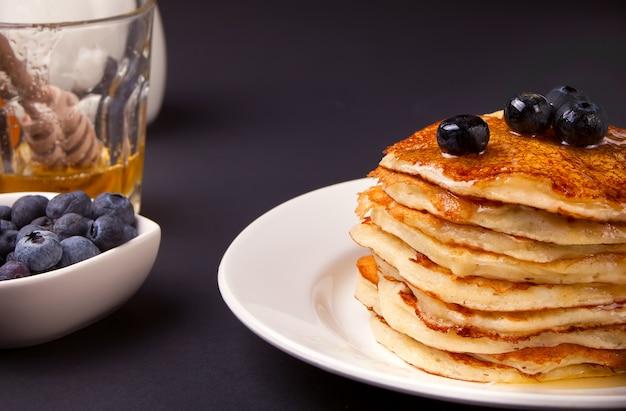 Pfannkuchen mit beeren und honig auf dem schwarzen hintergrund