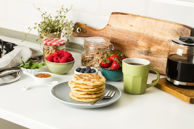 Pfannkuchen mit beeren und honig auf einem grauen teller und mit einer tasse kaffee auf einer küchentheke