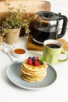 Pfannkuchen mit beeren und honig auf einem grauen teller und mit einer tasse kaffee