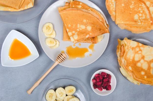 Pfannkuchen mit beeren und honig zum frühstück auf grauem tisch