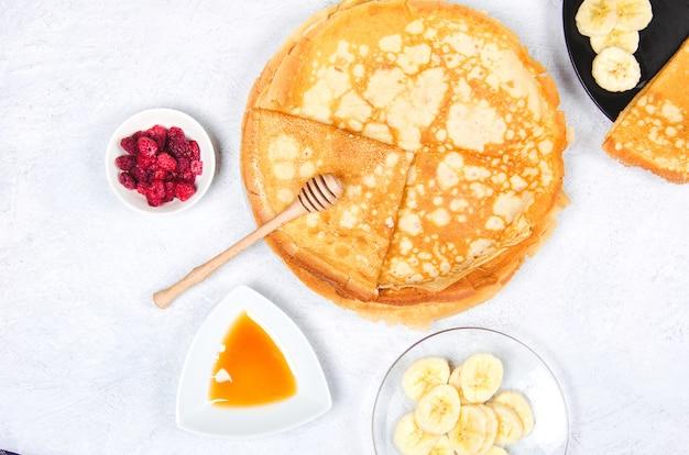Pfannkuchen mit beeren und honig zum frühstück auf weißem tisch