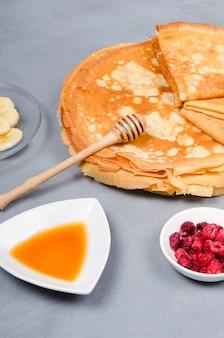 Pfannkuchen mit beeren und honig zum frühstück auf weißgrauem tisch