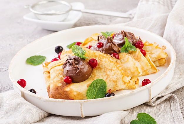 Pfannkuchen mit beeren und schokolade mit minzblatt verziert. leckeres frühstück.