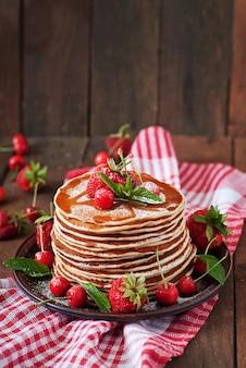 Pfannkuchen mit beeren und sirup im rustikalen stil