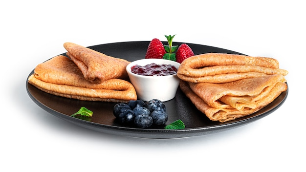 Pfannkuchen mit beerenmarmelade isoliert. pfannkuchen mit erdbeeren und blaubeeren auf schwarzem teller.