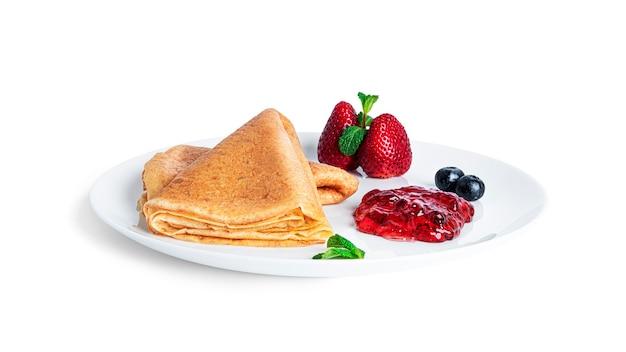 Pfannkuchen mit beerenmarmelade isoliert. pfannkuchen mit erdbeeren und blaubeeren auf weißem teller.