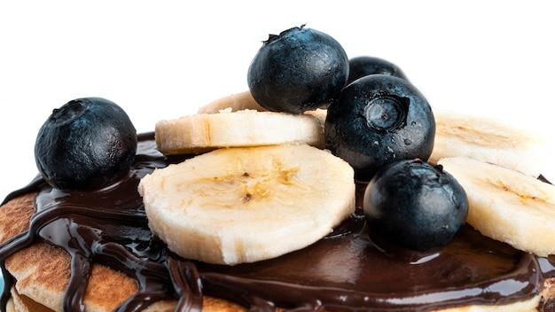 Pfannkuchen mit blaubeeren, banane und schokolade lokalisiert auf weiß.