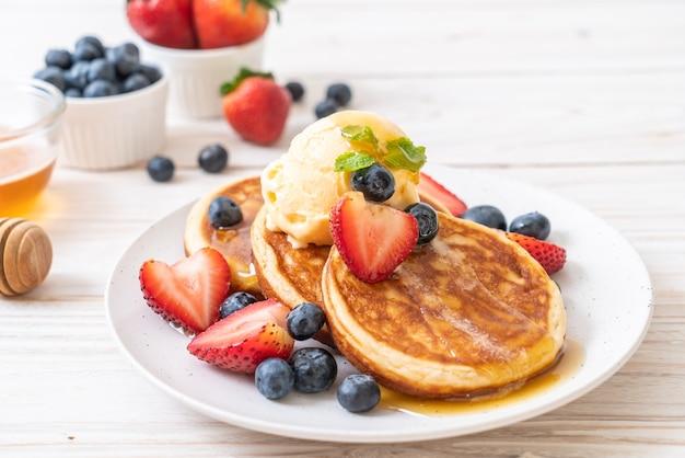 Pfannkuchen mit blaubeeren, erdbeeren, honig und vanilleeis