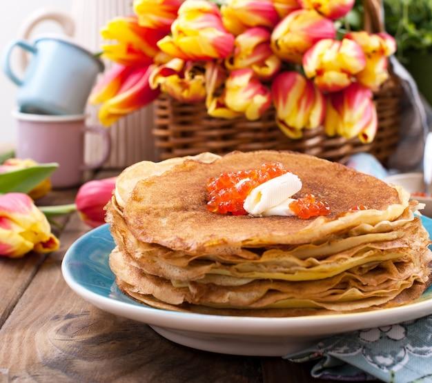 Pfannkuchen mit butter und kaviar auf einem hölzernen hintergrund und einem blumenstrauß von gelben tulpen.