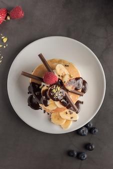 Pfannkuchen mit erdbeeren, himbeeren, banane, schokolade, pistazien und sahne auf einem weißen teller.