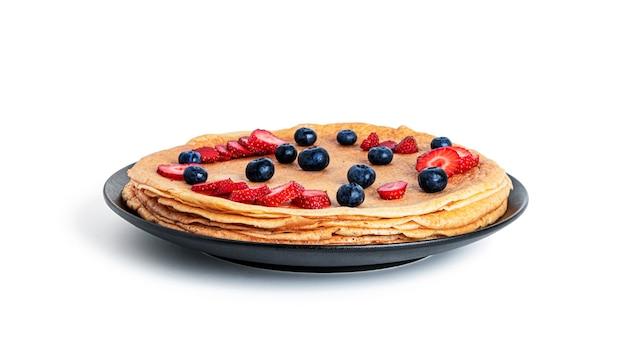 Pfannkuchen mit erdbeeren und blaubeeren isoliert.