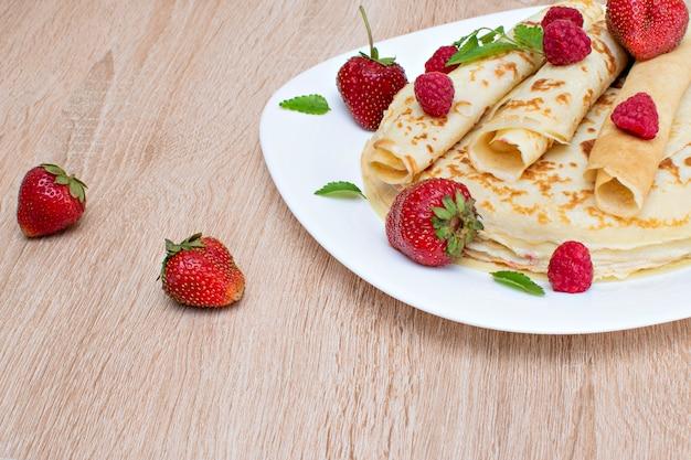 Pfannkuchen mit erdbeeren und himbeeren auf einem teller