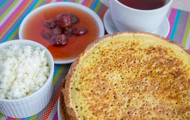 Pfannkuchen mit erdbeermarmelade, käse und einer tasse tee.