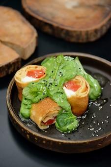 Pfannkuchen mit fischlachs, käse und spinat. speisekarte
