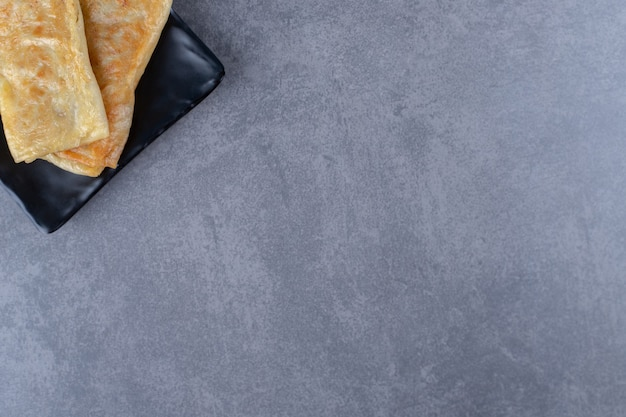 Pfannkuchen mit fleisch auf der holzplatte auf marmortisch.