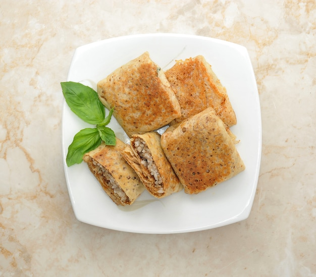 Pfannkuchen mit fleisch auf weißer platte