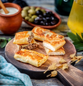 Pfannkuchen mit fleisch und hüttenkäse auf einem hölzernen brett