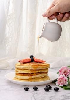 Pfannkuchen mit frischen beeren und ahornsirup mit sirup übergießen