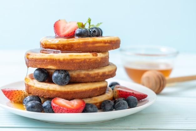 Pfannkuchen mit frischen blaubeeren, frischen erdbeeren und honig