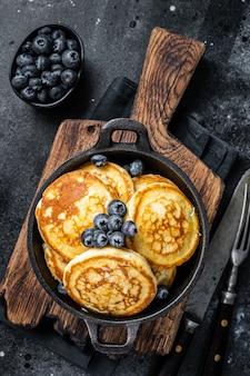 Pfannkuchen mit frischen blaubeeren und ahornsirup in einer pfanne. schwarzer hintergrund. ansicht von oben.