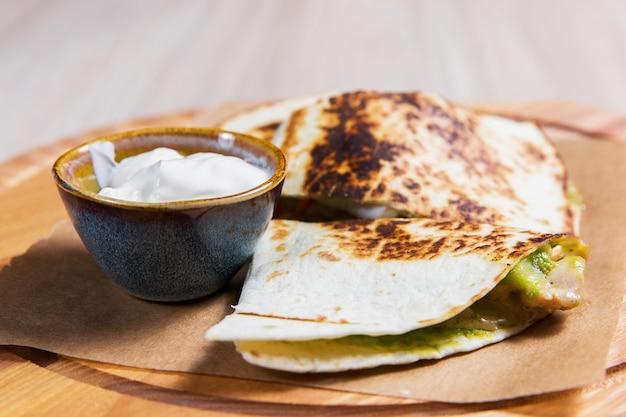 Pfannkuchen mit gemüse und weißer soße auf holztisch in einem restaurant. gesundes essen