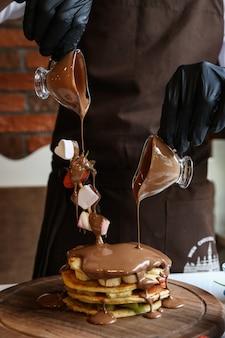 Pfannkuchen mit geschnittener banane und kiwi mit geschmolzener schokolade