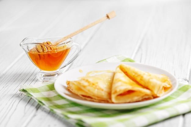 Pfannkuchen mit honig auf dem tisch