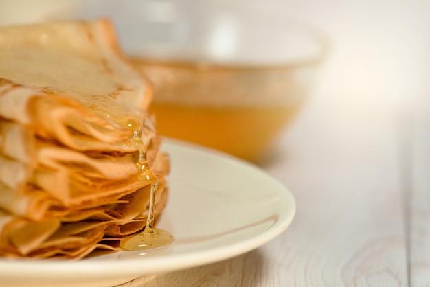 Pfannkuchen mit honig, sauerrahm und milch auf einem hellen holztisch