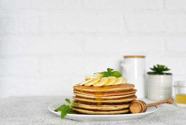 Pfannkuchen mit honig und bananen zum frühstück auf dem küchentisch.