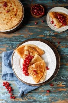 Pfannkuchen mit honig und roten johannisbeeren auf weißem teller maslenitsa