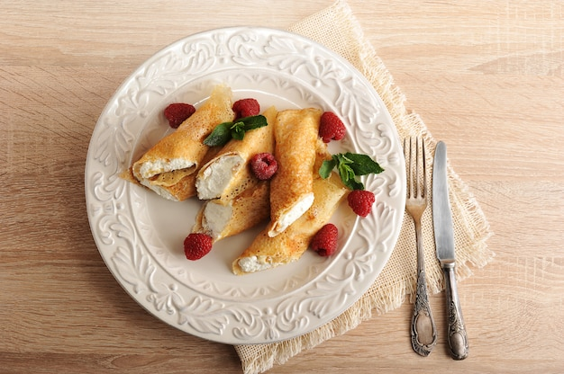 Pfannkuchen mit hüttenkäse und himbeeren auf einer platte