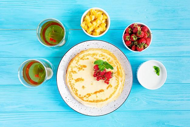 Pfannkuchen mit karamellisierten äpfeln, himbeeren, erdbeeren und roten johannisbeeren