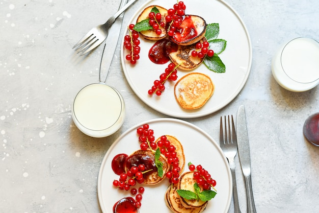 Pfannkuchen mit kirschmarmelade und roter johannisbeere auf weißem teller