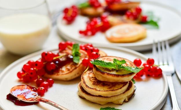 Pfannkuchen mit kirschmarmelade und roter johannisbeere auf weißer handwerksplatte