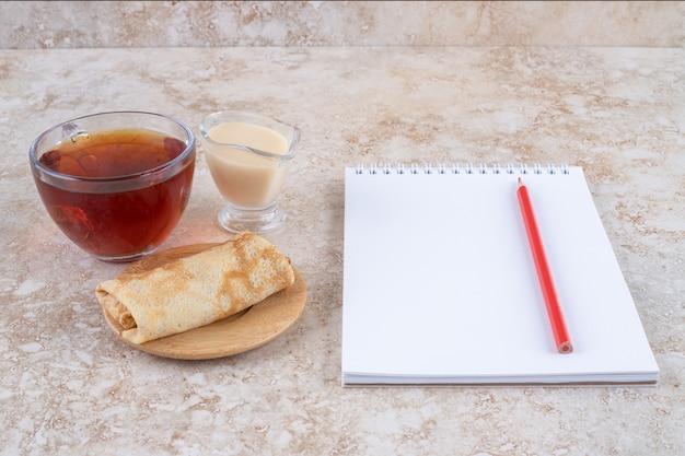 Pfannkuchen mit kondensmilch und einer tasse tee