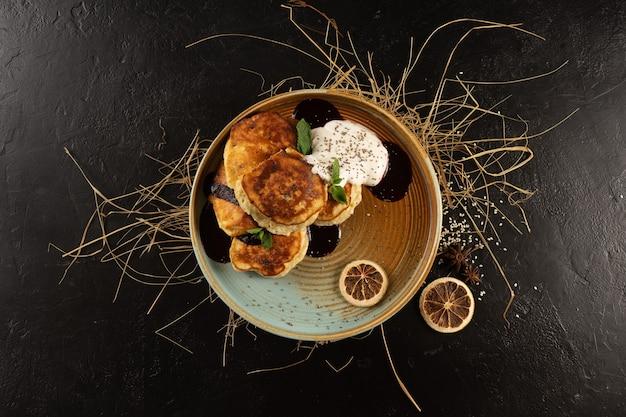 Pfannkuchen mit marmelade, joghurt und chiasamen, garniert mit minzblättern, zitronenscheiben und sternanis auf einem runden farbigen teller.