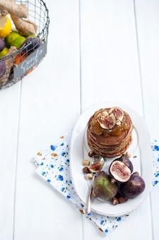 Pfannkuchen mit marmelade und feigen auf einem weißen teller und obst