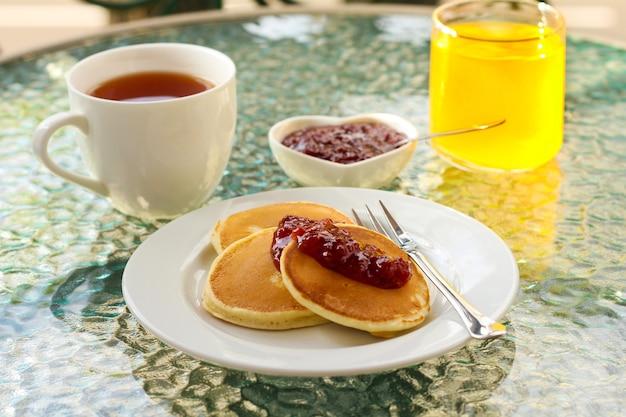 Pfannkuchen mit marmeladentee und saft auf dem tisch auf dem balkon