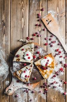 Pfannkuchen mit moosbeeren und sauerrahm auf einem hölzernen brett im mehl