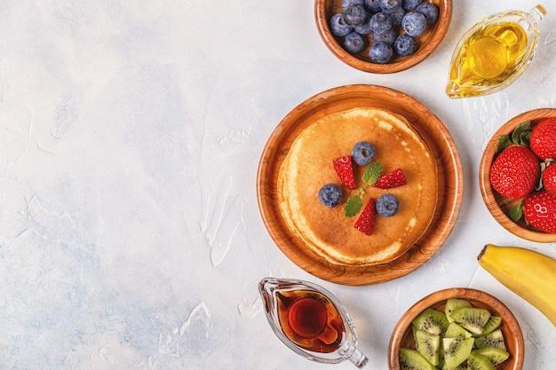 Pfannkuchen mit obst, honig, ahornsirup