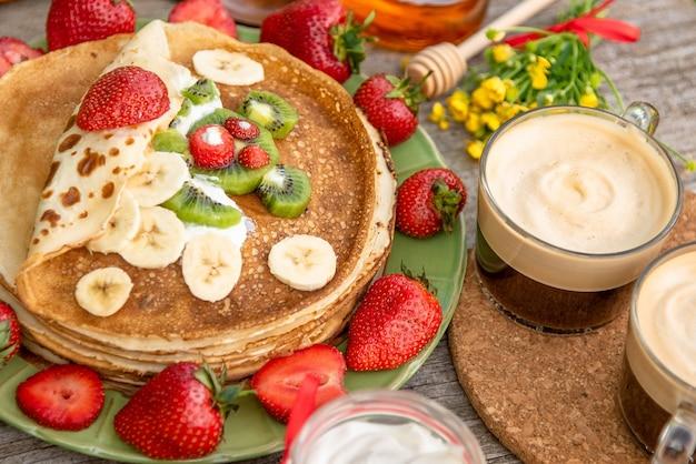 Pfannkuchen mit obst und kaffee zum frühstück.