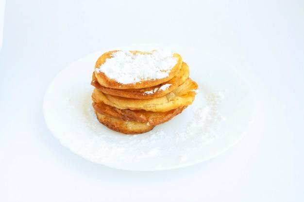 Pfannkuchen mit puderzucker auf einem teller, isoliert