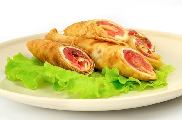 Pfannkuchen mit rotem fisch auf einem stück salat lokalisiert auf weiß.