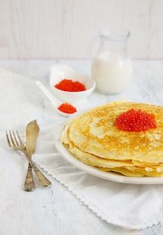 Pfannkuchen mit rotem kaviar auf dem weißen hintergrund