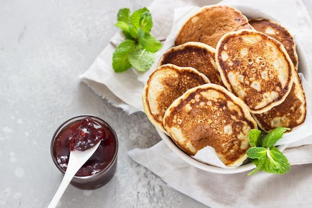 Pfannkuchen mit roter beerenmarmelade und minze, hellgrauer steinhintergrund amerikanische küche. frühstück.