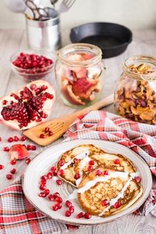 Pfannkuchen mit sauerrahm- und granatapfelsamen auf einer platte