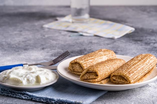 Pfannkuchen mit saurer sahne auf einem teller. russische küche. maslenitsa.